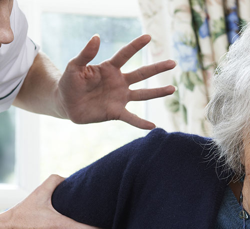 a nursing home staff member reaching out to put a hand on an elderly person